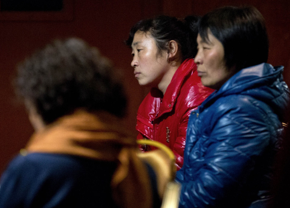 Photo - Chinese relatives of passengers aboard a missing Malaysia Airlines plane wait inside a hotel room in Beijing Monday, March 10, 2014. The anguished hours had turned into a day and a half. Fed up with awaiting word on the missing plane, relatives of passengers in Beijing lashed out at the carrier with a handwritten ultimatum and an impromptu news conference. (AP Photo/Andy Wong)