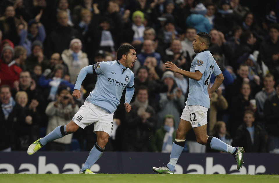 Photo -   Manchester City's Carlos Tevez, left, celebrates with teammate Gael Clichy after scoring against Swansea during their English Premier League soccer match at The Etihad Stadium, Manchester, England, Saturday, Oct. 27, 2012. (AP Photo/Jon Super)