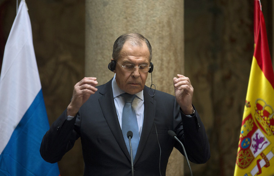 Photo - Russian Foreign Minister Sergey Lavrov raises his hands to take off his headphones at the end of a news conference at the Spanish foreign ministry in Madrid, Spain Wednesday March 5, 2014. Lavrov held talks on the Ukraine crisis with European Union High Representative Catherine Ashton in Madrid on Tuesday, and met with Spanish Prime Minister Mariano Rajoy and later King Juan Carlos. Tension has risen in recent weeks with Western countries backing the country's new caretaker government while Moscow accuses them of supporting an anti-constitutional coup and pledges to protect Russians in Ukraine. (AP Photo/Paul White)