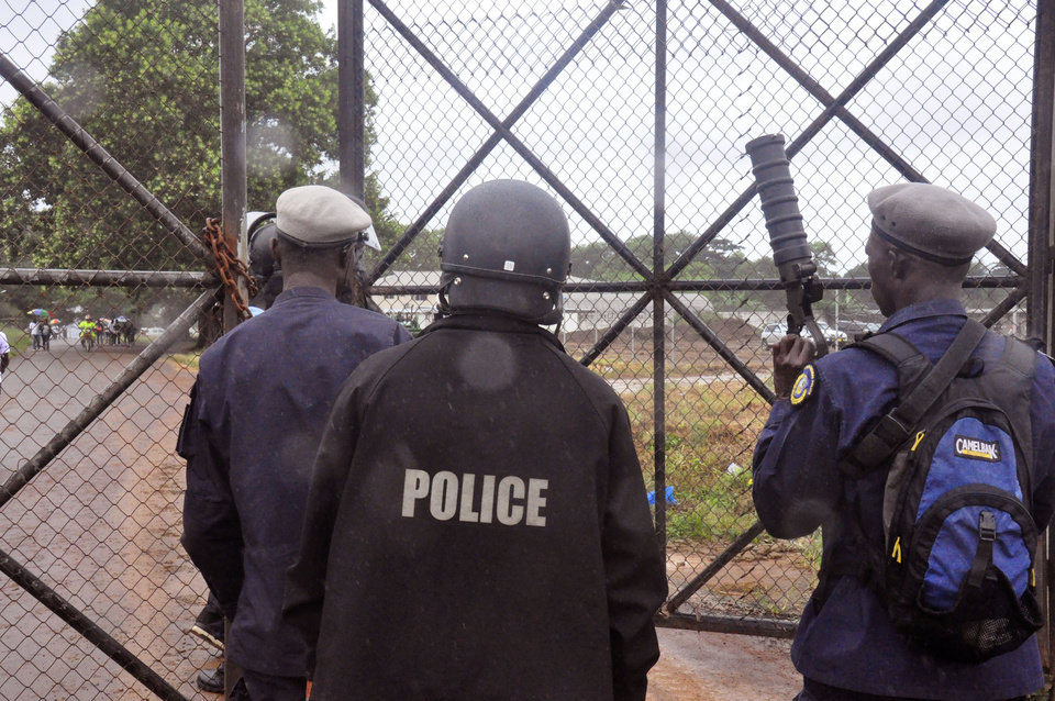 Photo - Liberian Police dressed in riot gear deploy at a MSF, 'Doctors Without Borders', Ebola treatment center, in the rain, as they provide security in the city of Monrovia, Liberia, Monday, Aug. 18, 2014. Liberia's armed forces were given orders to shoot people trying to illegally cross the border from neighboring Sierra Leone, which was closed to stem the spread of Ebola, local newspaper Daily Observer reported Monday. (AP Photo/Abbas Dulleh)
