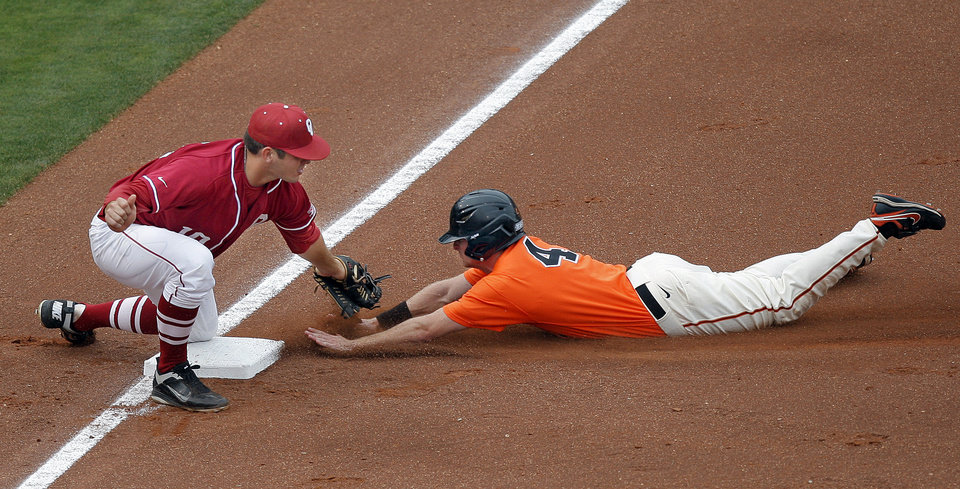 Oklahoma State's Saulyer Saxon slides into third base as Oklahoma's Garrett Carey tries to tag him during the Bedlam baseball game between the University of Oklahoma and Oklahoma State University at the Chickasaw Bricktown Ballpark in Oklahoma City, Sunday, May 6, 2012. Photo by Sarah Phipps, The Oklahoman