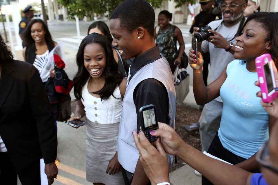 Photo -   Gabby Douglas, left, 2012 London Summer Olympics gold medal-winning gymnast, laughs with her brother, John Douglas, after arriving at Norfolk International Airport, Thursday, Aug. 16, 2012, in Norfolk, Va., on her way to visit her hometown of Virginia Beach, Va. (AP Photo/Virginian-Pilot, Ross Taylor) MAGS OUT