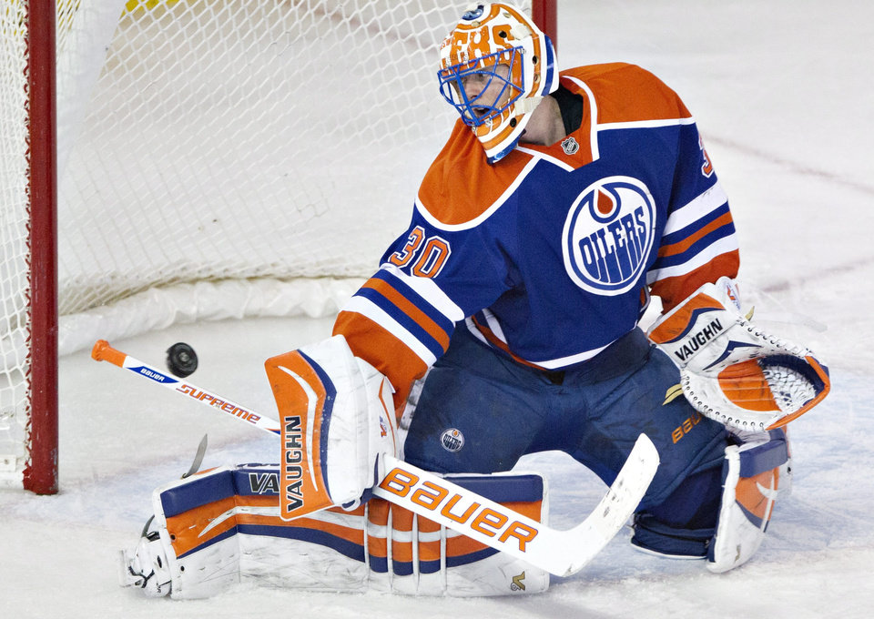 Photo - Edmonton Oilers' Ben Scrivens (30) makes a save against the Anaheim Ducks during second-period NHL hockey game action in Edmonton, Alberta, Friday, March 28, 2014. (AP Photo/The Canadian Press, Jason Franson)
