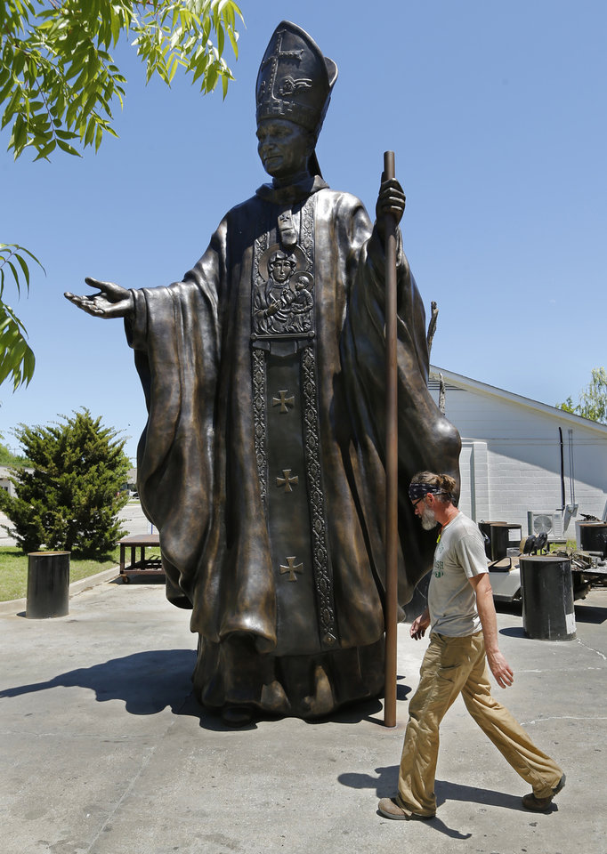 Photo -  Foundry worker Scott Adams is dwarfed by artist Teresa Clark's 21-foot statue of Pope John Paul II at The Crucible in Norman. [PHOTO BY STEVE SISNEY, THE OKLAHOMAN]