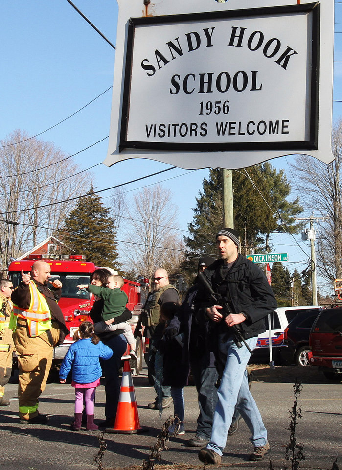 Photo - Parents walk past police and firefighters away from the Sandy Hook Elementary School with their children following a shooting at the school, Friday, Dec. 14, 2012 in Newtown, Conn. A man opened fire inside the Connecticut elementary school where his mother worked Friday, killing 26 people, including 20 children, and forcing students to cower in classrooms and then flee with the help of teachers and police. (AP Photo/The Journal News, Frank Becerra Jr.) MANDATORY CREDIT, NYC OUT, NO SALES, TV OUT, NEWSDAY OUT; MAGS OUT ORG XMIT: NYWHI121