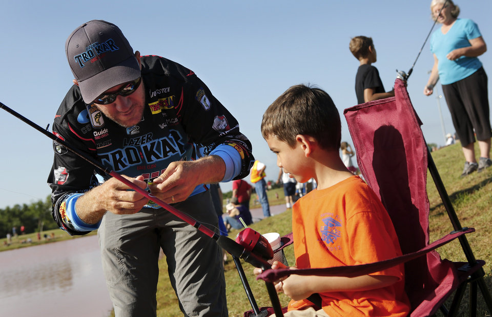 Photo - 2012 Bassmaster Angler of the Year Brent Chapman, from Lake Quivira, KS, puts bait on the hook for 6 year-old angler Tristan Perez of Moore. Moore hosted its annual kids fishing derby Saturday morning, July 27, 2013,  at Buck Thomas Park.  As part of the event this year, a charity called the Tackle the Storm Foundation handed out rods and reels to tornado victims. Several bass fishing pros from Oklahoma attended the event to help distribute the fishing equipment and share fishing tips with the young anglers. An event official  said about 250 children participated in the fishing derby. Photo  by Jim Beckel, The Oklahoman.