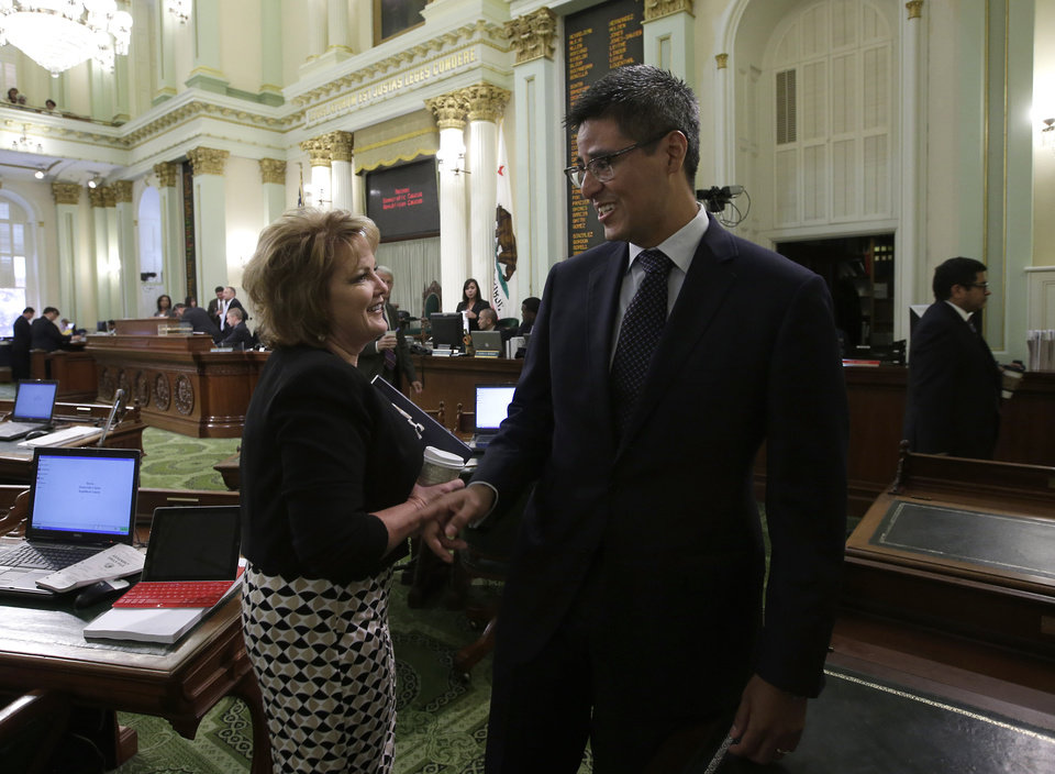 Photo - FILE - In this Aug. 11, 2014 file photo Assemblywoman Shannon Grove, R-Bakersfield, talks with Assemblyman Henry Perea, D-Fresno, at the Capitol in Sacramento, Calif. Despite a bipartisan push, the Senate's Democratic leaders have so far derailed efforts to halt an increase in the price of gasoline and other fuels that will hit consumers in January. Perea's bill, AB69, that would delay putting fuels under the cap-and-trade program until Jan. 1, 2018 has been held up by the Senate Rules Committee because the measure was amended after the normal deadline. (AP Photo/Rich Pedroncelli, File)
