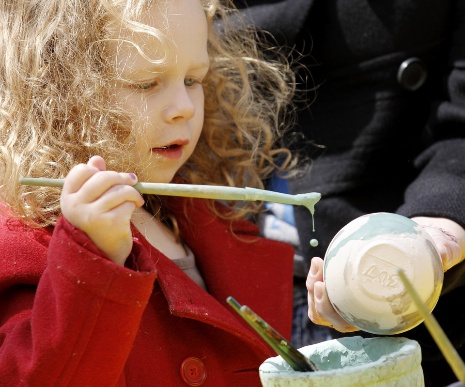 Photo - Paisley Hunter, 3, paints a clay bowl while her mother, Erin Hunter, holds it for her at the Pottery Place at the Festival of the Arts in downtown Oklahoma City  Wednesday, April 24, 2013. The Hunters are from Piedmont. Photo by Doug Hoke, The Oklahoman