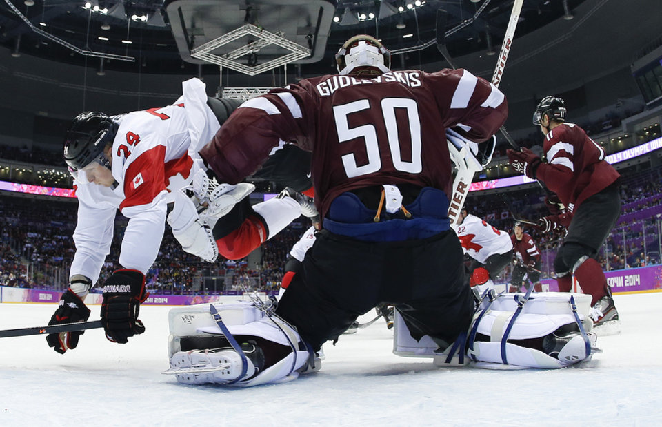 Photo - Canada forward Corey Perry trips over Latvia goaltender Kristers Gudlevskis in the first period of a men's ice hockey game at the 2014 Winter Olympics, Wednesday, Feb. 19, 2014, in Sochi, Russia. (AP Photo/Julio Cortez, Pool)