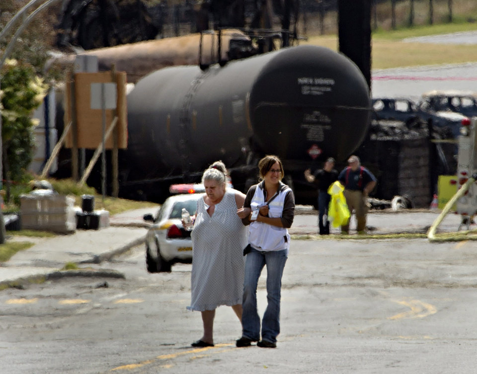 Photo - A volunteer escorts an evacuee to pick up supplies from her home near the blast site Monday, July 8, 2013, in Lac-Megantic, Quebec. A runaway train derailed Saturday in Lac-Megantic, igniting tanker cars carrying crude oil. (AP Photo/The Canadian Press, Ryan Remiorz)