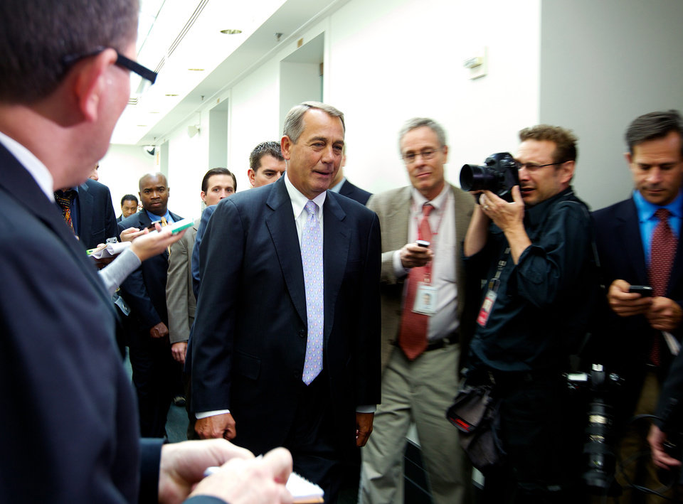 Photo - House Speaker John Boehner of Ohio, walks out of a Republican caucus at the U.S. Capitol in Washington, Saturday, Sept. 28, 2013.  Lawmakers from both parties urged one another in a rare weekend session to give ground in their fight over preventing a federal shutdown, with the midnight Monday deadline fast approaching.  (AP Photo/Molly Riley)