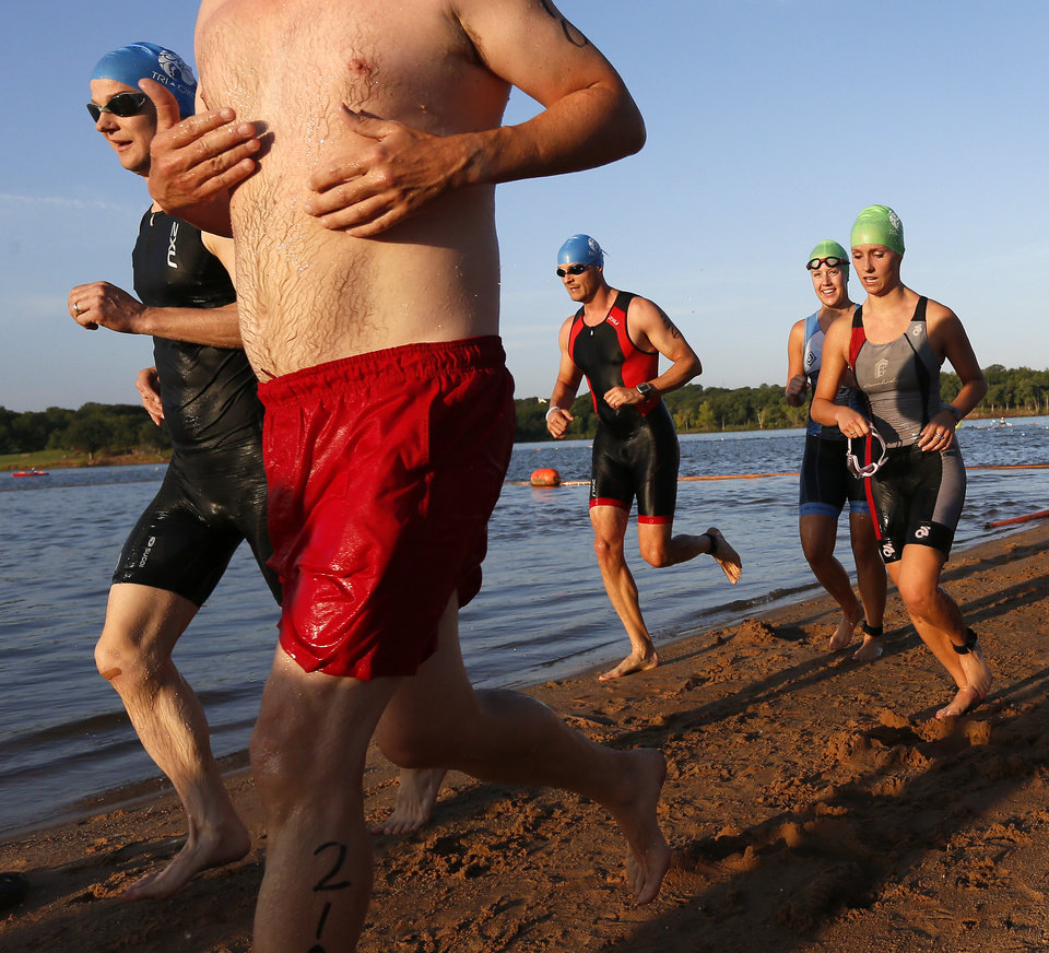 Photo -  Competitors run along the beach during the Arcadia Lake Triathlon and Aquabike at Edmond Park. PHOTO BY NATE BILLINGS, THE OKLAHOMAN   NATE BILLINGS -