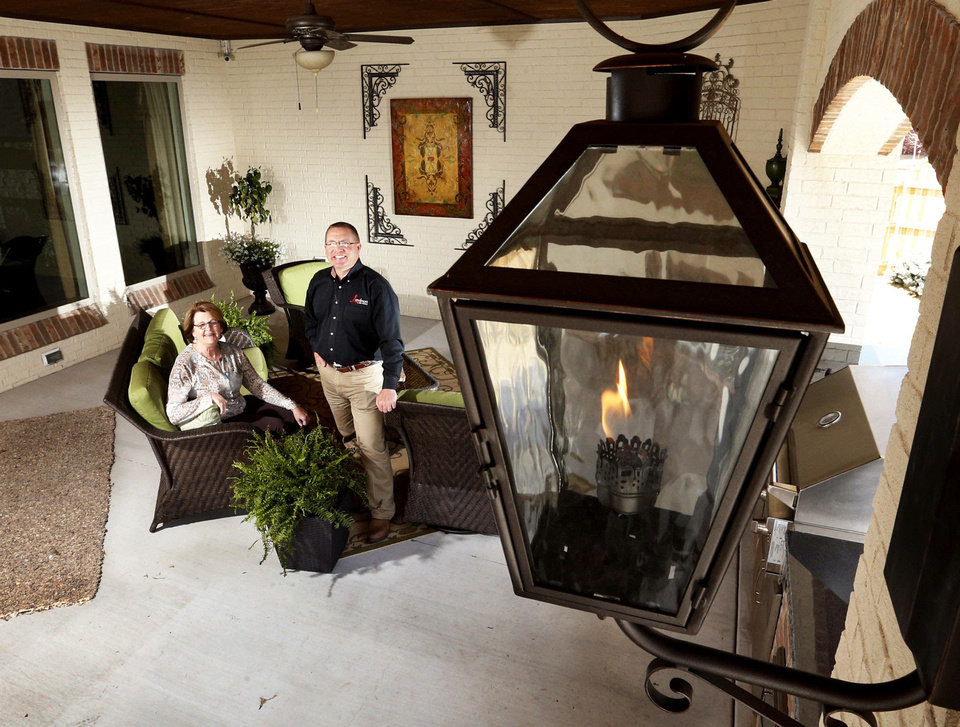 Pam Hall of Oklahoma Natural Gas and Dan Reeves of Landmark Fine Homes show the outdoor living area featuring gas light fixtures and a gas log fireplace at a Landmark model home at 4500 Northfields in Norman's Carrington Lakes neighborhood. Photos by STEVE SISNEY, THE OKLAHOMAN