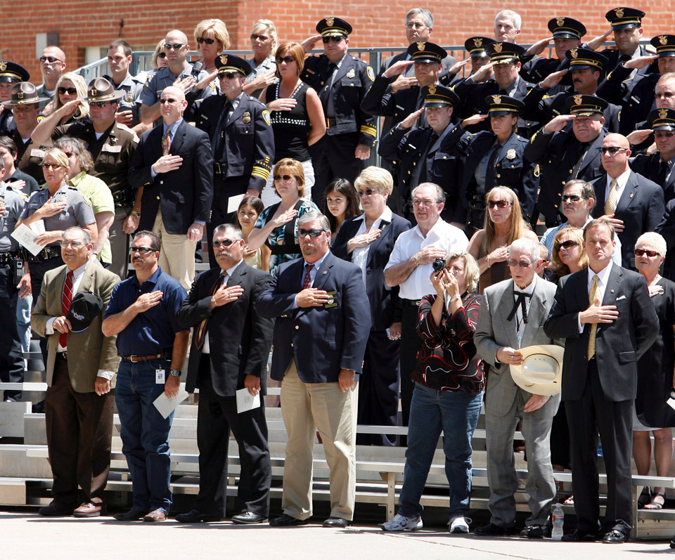 Photo - Family, and law enforcement personnel attend a memorial for fallen officers in front of Oklahoma City Police Headquarters in Oklahoma City, Oklahoma on Friday, May 9, 2008.  Front row second from right is former Oklahoma County District Attorney Bob Macy. BY STEVE SISNEY, THE OKLAHOMAN