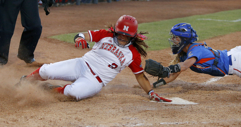 Nebraska's Tatum Edwards scores past Florida's Aubree Munro in the seventh inning during the Women's College World Series softball game between Nebraska and Florida at ASA Hall of Fame Stadium in Oklahoma City, Saturday, June, 1, 2013. Photo by Bryan Terry, The Oklahoman