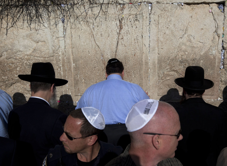 Photo -   New Jersey Gov. Chris Christie, center, touches the stones of the Western Wall, the holiest site where Jews can pray, during his visit to Jerusalem's old city, Monday, April 2, 2012. Christie kicked off his first official overseas trip Monday meeting Israel's leader in a visit that may boost the rising Republican star's foreign policy credentials ahead of November's presidential election. (AP Photo/Sebastian Scheiner)