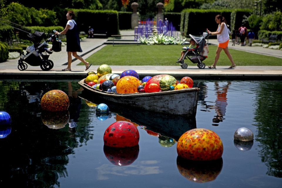 Photo - Visitors walk past a boat of blown glass orbs that are part of an exhibit of Dale Chihuly's art at the Dallas Arboretum on Friday, May 4, 2012. Photo by Bryan Terry, The Oklahoman  BRYAN TERRY - THE OKLAHOMAN