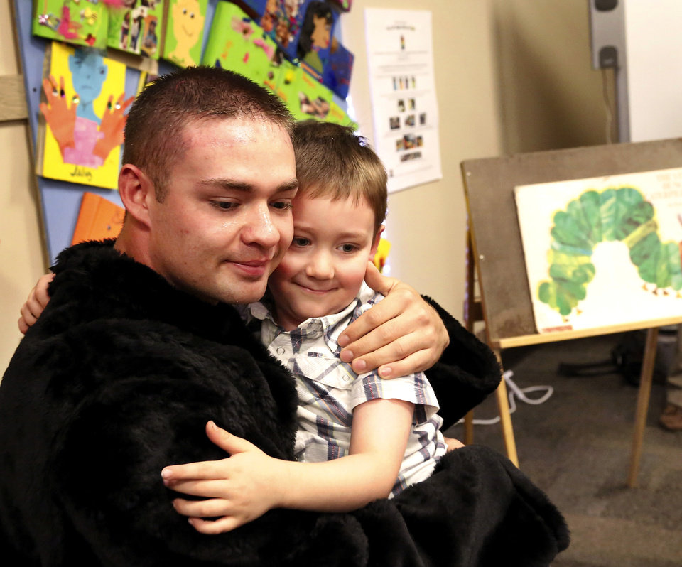 """Chad Chudoba and son, Isaac, hug after being re-united. U.S. Army Sgt. Chad Chudoba arrived at Del City Elementary School Monday morning, Sep. 30, 2013, to see his five year-old son for the first time in more than nine months. Before re-uniting with his son, Sgt. Chudoba disguised himself as the school\'s mascot, stepping into a full-body panther costume and reading a book to his son, Isaac\'s kindergarten classmates who had assembled on the floor of the school\'s library for story time. When he finished the story, Sgt. Chudoba rose from the small chair and removed the head of the mascot and told the giggling kindergarteners he wasn\'t really a panther, and proudly announced, """"I am really Isaac\'s dad."""" Then, he extended his arm toward the boy wearing rolled-up jeans and a western style, pearl-snap shirt near the front of the group, and clasped his son\'s small hand into his as he pulled the boy onto his lap and hugged him. Chudoba is a member of the Army\'s 1245th transportation company and returned Saturday after serving with his unit in Afghanistan for 9 months. After the reunion, the younger Chudoba admitted he thought the voice of the panther sounded much like his dad\'s, but the biggest clue for the kindergartener that this was no ordinary mascot were its hands. He told his dad he recognized his hands as he listened to the story and watch the mascot turn the pages of the book. Photo by Jim Beckel, The Oklahoman."""