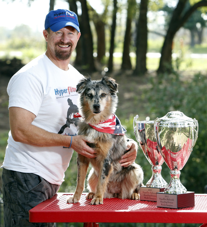 Photo - Lee Fairchild and his dog, Gracie, show their national dog disc trophies from 2010 and 1012.  Photo by Steve Sisney, The Oklahoman