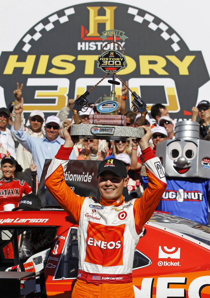 Photo - Kyle Larson raises the trophy in Victory Lane after winning the NASCAR Nationwide series auto race at Charlotte Motor Speedway in Concord, N.C., Saturday, May 24, 2014. (AP Photo/Terry Renna)
