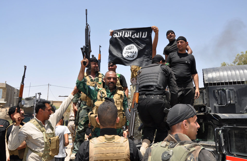 Photo - In this Saturday, June 28, 2014 photo, Iraqi security forces hold up a flag of the Islamic State in Iraq and the Levant they captured during an operation to regain control of Dallah Abbas north of Baqouba, the capital of Iraq's Diyala province, 35 miles (60 kilometers) northeast of Baghdad, Iraq. The Islamic State, which already controls vast swaths in northern and eastern Syria amid the chaos of that nation's civil war, aims to erase the borders of the modern Middle East and impose its strict brand of Shariah law. (AP Photo)