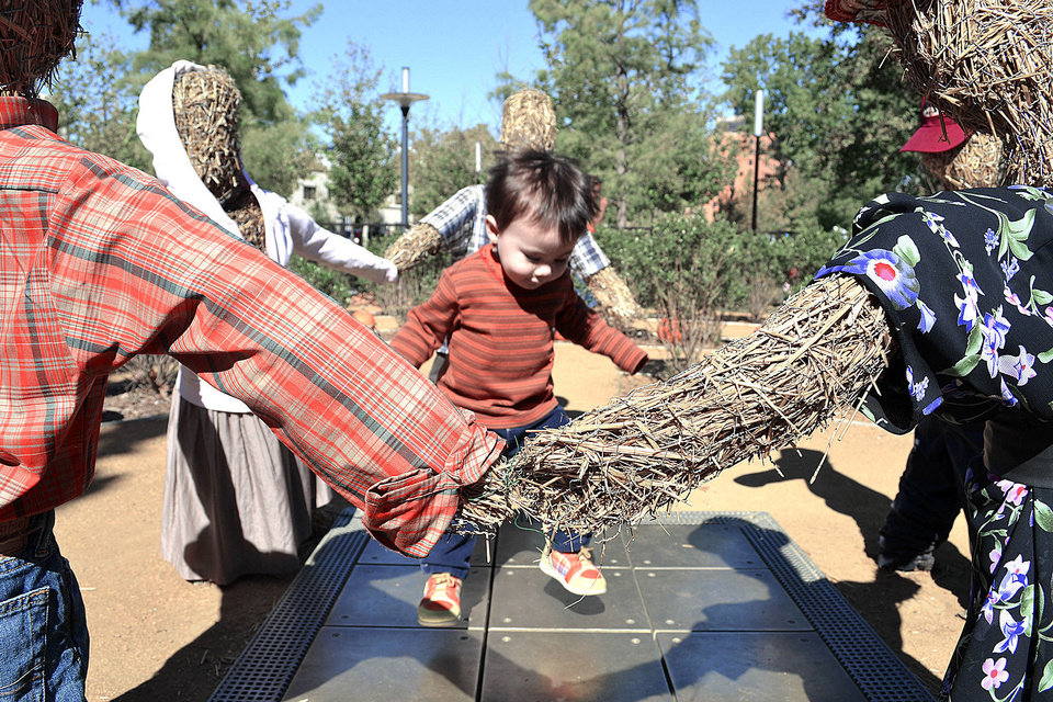 Photo - Above: One-year-old Kurtis Wenzel, of Edmond, makes music with his feet Saturday at the Myriad Botanical Gardens in downtown Oklahoma City.