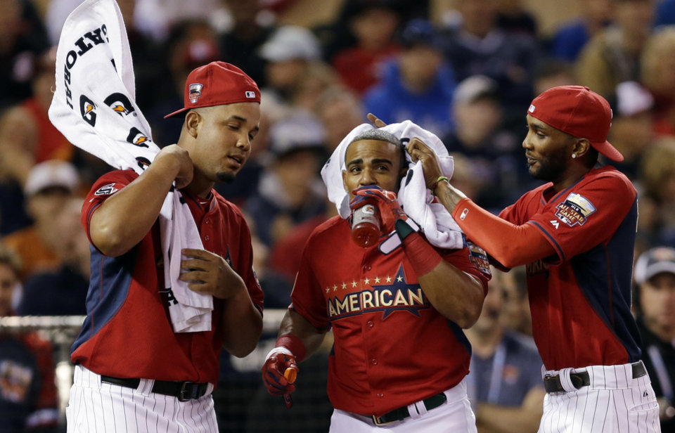 Photo - Teammates cool off American League's Yoenis Cespedes, of the Oakland Athletics, center, between pitches during the MLB All-Star baseball Home Run Derby, Monday, July 14, 2014, in Minneapolis. (AP Photo/Jeff Roberson)