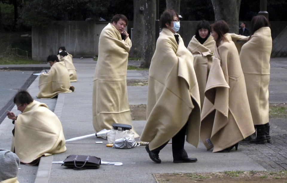 Photo - Stranded commuters wrap themselves in blankets bracing for chilly evening at a park in Yokohama, near Tokyo, following a strong earthquake hit eastern Japan on Friday, March 11, 2011. (AP Photo/Shuji Kajiyama) ORG XMIT: XKAJ103