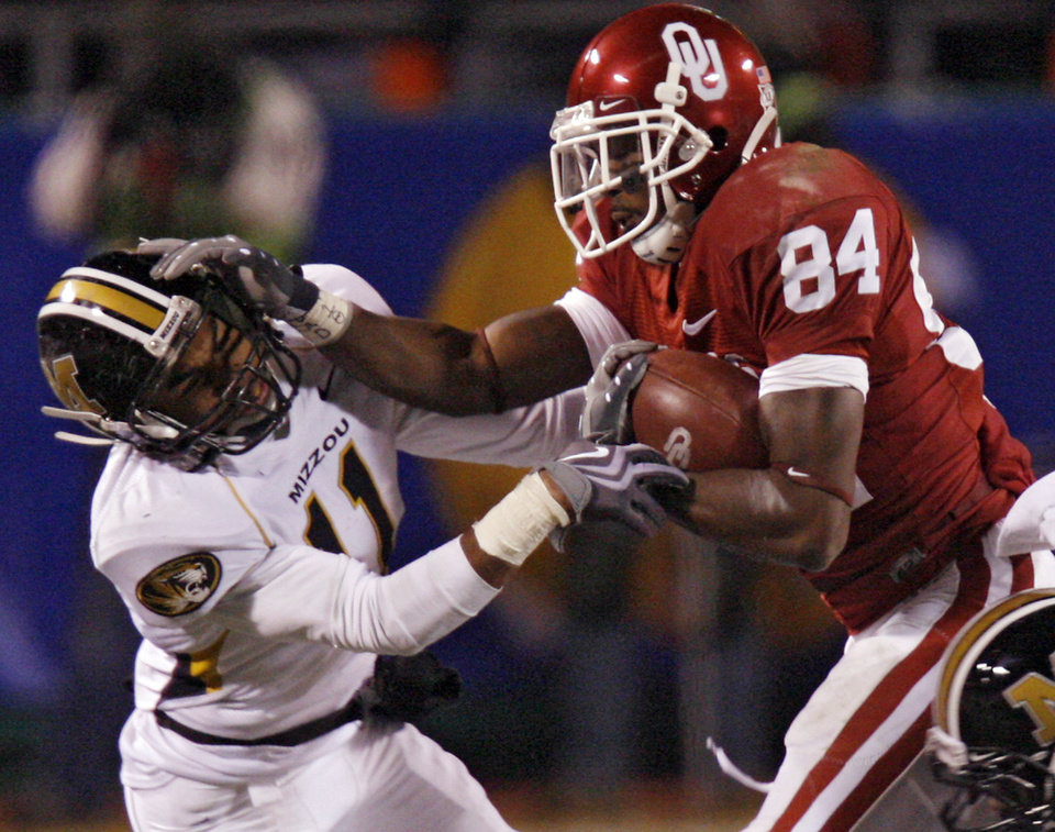 Photo - Oklahoma's Quentin Chaney (84) stiff arms Missouri's Tru Vaughns (11) during the first half of the Big 12 Championship college football game between the University of Oklahoma Sooners (OU) and the University of Missouri Tigers (MU) on Saturday, Dec. 6, 2008, at Arrowhead Stadium in Kansas City, Mo. 