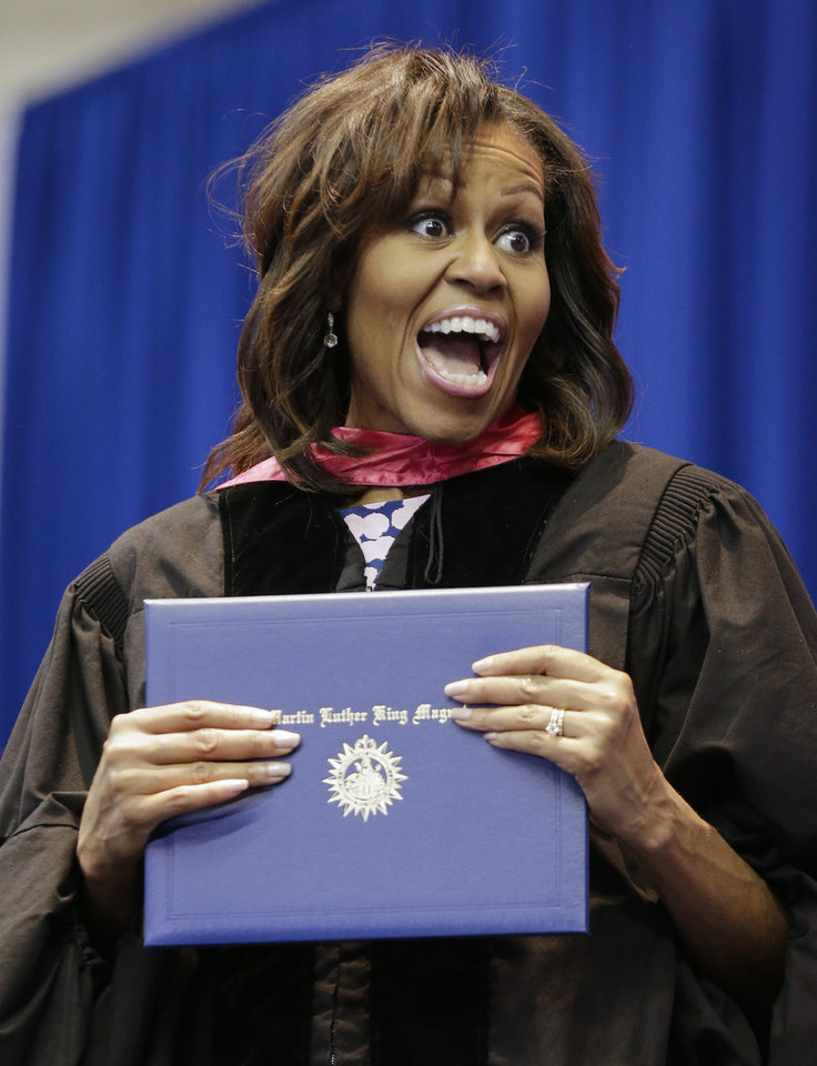 Photo - First lady Michelle Obama jokes with a student as she hands out diplomas during the graduation ceremony for Martin Luther King, Jr. Academic Magnet High School on Saturday, May 18, 2013, in Nashville, Tenn. (AP Photo/Mark Humphrey)