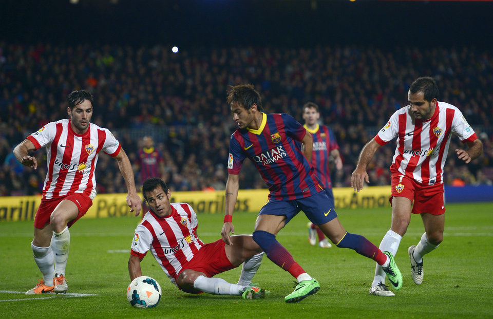 Photo - FC Barcelona's Neymar, from Brazil, second right, duels for the ball against Almeria's Rafael Ramos. second left, during a Spanish La Liga soccer match at the Camp Nou stadium in Barcelona, Spain, Sunday, March 2, 2014. (AP Photo/Manu Fernandez)
