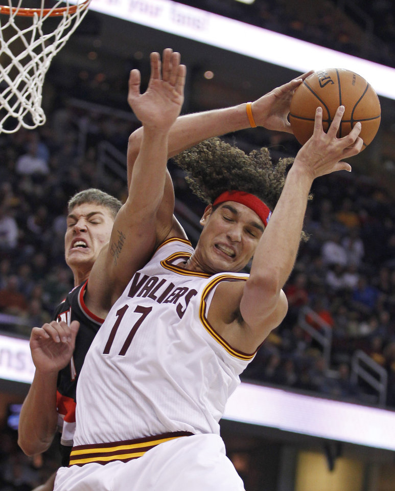 Photo - Cleveland Cavaliers' Anderson Varejao (17), from Brazil, grabs a rebound ahead of Portland Trail Blazers' Meyers Leonard (11) in the second quarter of an NBA basketball game Saturday, Dec. 1, 2012, in Cleveland. (AP Photo/Tony Dejak)