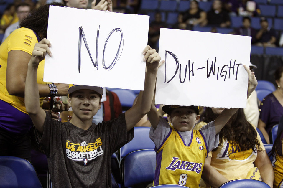Photo - Los Angeles Lakers fans 12-year-old Ian Klock and his 9-year-old brother Nate Klock, both from Upland, Calif., display posters about Dwight Howard, prior to the Lakers' NBA basketball preseason game against the Golden State Warriors on Saturday, Oct. 5, 2013, in Ontario, Calif.  (AP Photo/Alex Gallardo)