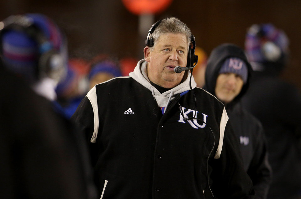 Photo - FILE - In this Nov. 23, 2013, file photo, Kansas head coach Charlie Weis looks at the score board late in the second half of their loss to Iowa State in an NCAA football game in Ames, Iowa. Coaches often say they are always on the hot seat. That might be true, but some seats are hotter than others. A few coaches in high-profile positions heading into 2014 very much in need of winning records and quality victories. (AP Photo/Justin Hayworth, File)