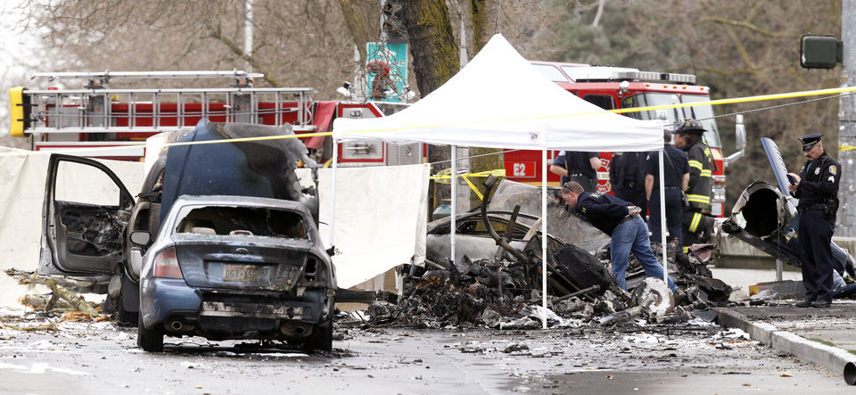 Photo - An investigator looks over the charred wreckage of a news helicopter and two vehicles after the chopper crashed into a city street near the Space Needle, Tuesday, March 18, 2014, in Seattle. Two people were killed and another critically injured. (AP Photo/Stephen Brashear)