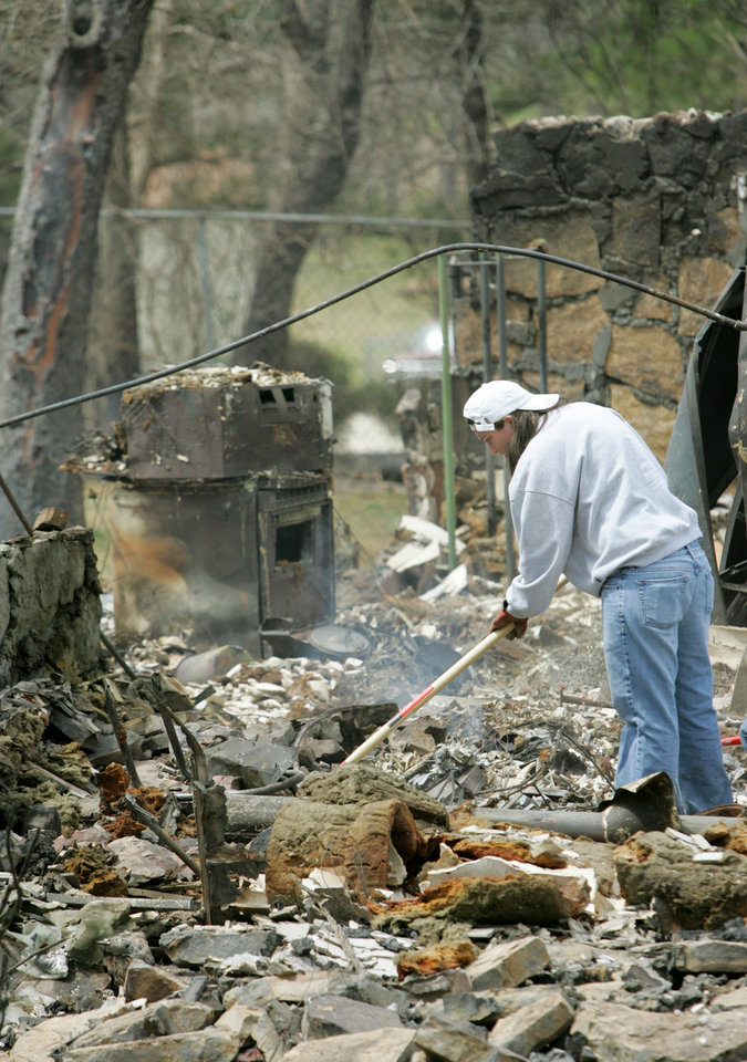 Sharon Smith searches for belongings at a friends parents home at 347 Ash road that was destroyed in a wildfire in Choctaw, Oklahoma April 10, 2009.  Photo by Steve Gooch, The Oklahoman