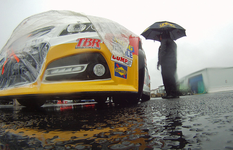 Photo - Pit crew members wait in the rain to push the car of J.J. Yeley into the inspection garage at the Talladega Superspeedway in Talladega, Ala., Saturday, May 4, 2013. Rain dampened Saturday's racing events at Talladega. (AP Photo/Dave Martin)