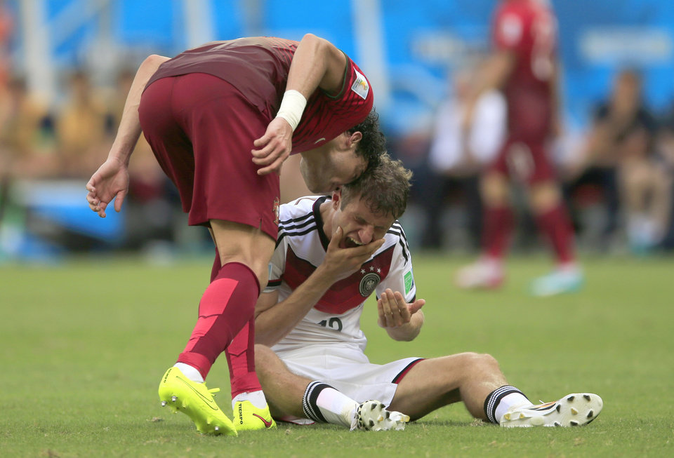 Photo - Portugal's Pepe , left, puts his head on Germany's Thomas Mueller during the group G World Cup soccer match between Germany and Portugal at the Arena Fonte Nova in Salvador, Brazil, Monday, June 16, 2014.  Pepe was red carded after this.  (AP Photo/Bernat Armangue)
