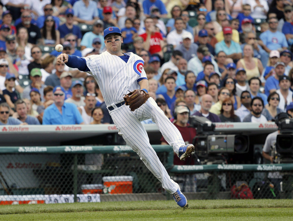 Photo - Chicago Cubs third baseman Mike Olt throws out Pittsburgh Pirates' Russell Martin after fielding Martin's sacrifice bunt during the second inning of a baseball game on Friday, June 20, 2014, in Chicago. (AP Photo/Charles Rex Arbogast)
