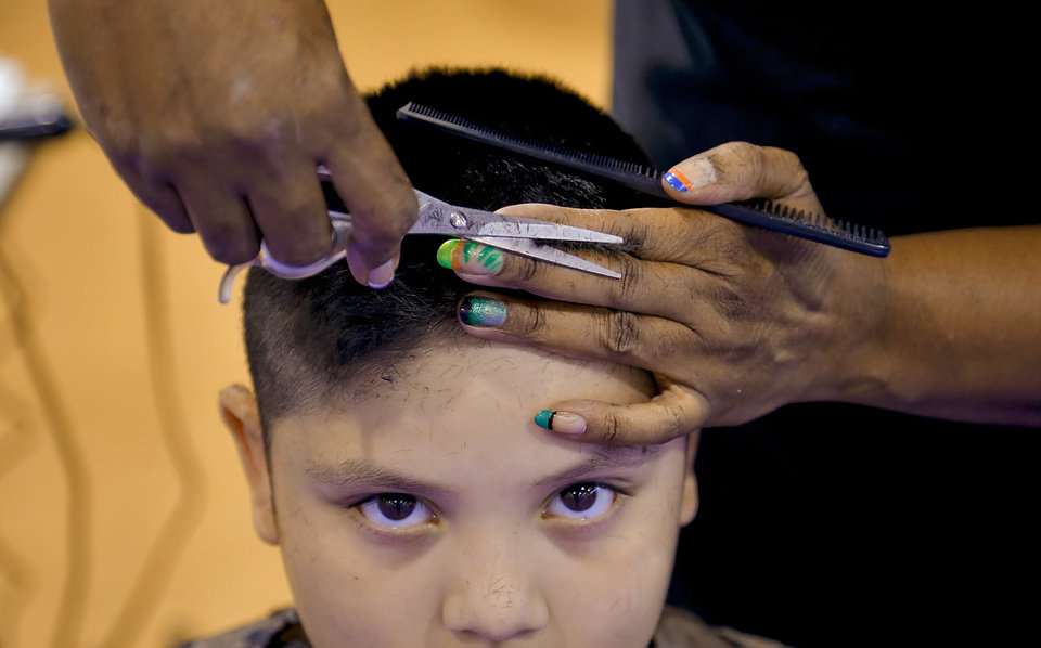 CHILD / CHILDREN / KIDS: Adan Ruiz, 8, gets a free haircut from nonprofit group Bound4Glory & Beyond at the Boys and Girls Club in Oklahoma City, Okla. on Monday, July 30, 2012.  The group provided the free haircuts to students before they start Oklahoma City Public School on August, 1st. Photo by Chris Landsberger, The Oklahoman