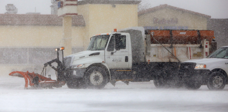 Photo -  A City of Edmond truck tries to clear Broadway during a snow storm in Edmond, Thursday, Dec. 24, 2009.  Photo by Bryan Terry, The Oklahoman
