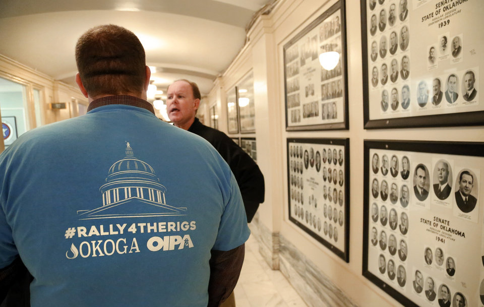 Photo -  Visitors representing oil and natural gas businesses in Oklahoma visit with each other outside lawmakers' offices in a hallway on the Senate side of the Capitol.