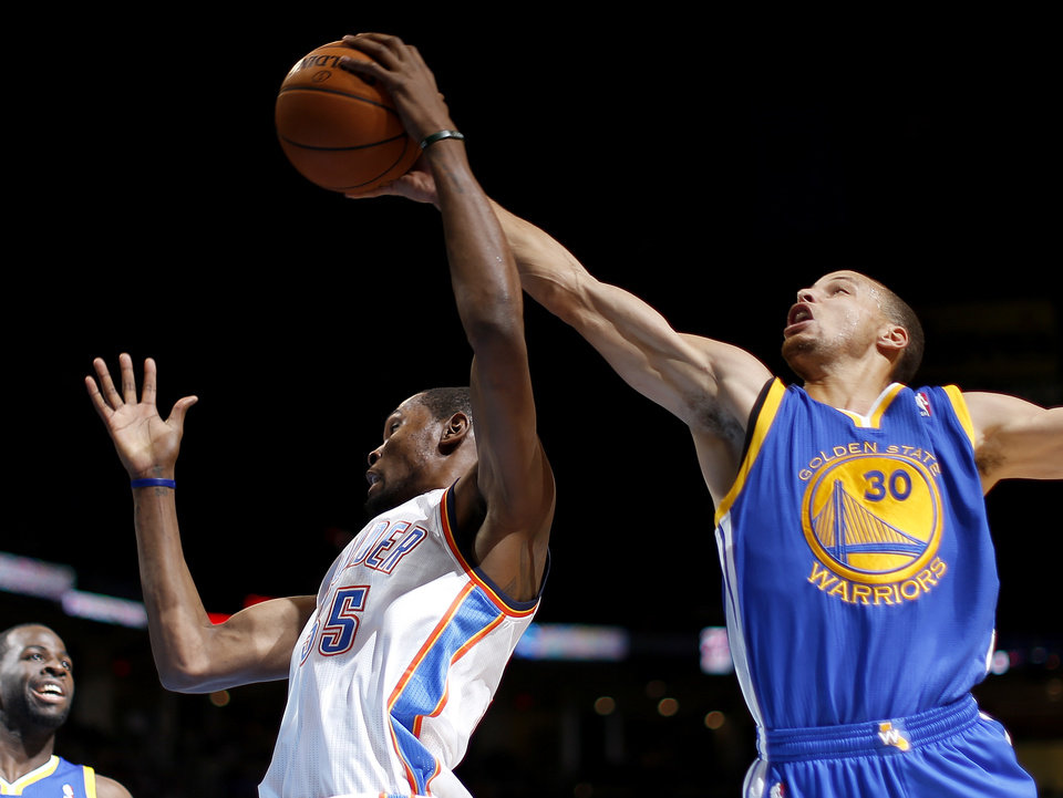 Photo - Oklahoma City's Kevin Durant (35) tries to grab a rebound beside Golden State's Stephen Curry (30) during an NBA basketball game between the Oklahoma City Thunder and the Golden State Warriors at Chesapeake Energy Arena in Oklahoma City, Friday, Jan. 17, 2014. Photo by Bryan Terry, The Oklahoman