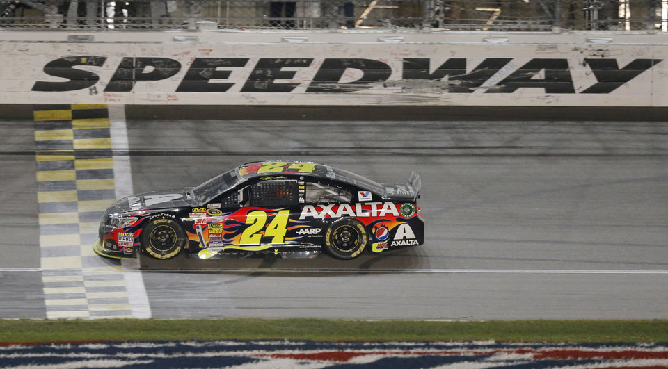 Photo - NASCAR driver Jeff Gordon (24) crosses the finish line to win the Sprint Cup Series auto race at Kansas Speedway in Kansas City, Kan., Saturday, May 10, 2014. (AP Photo/Orlin Wagner)