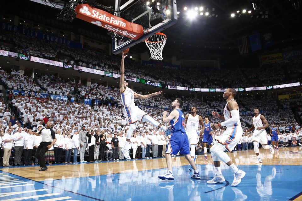 Photo - Thabo Sefolosha (25) shoots over J.J. Riddick (4) during Game 5 of the Western Conference semifinals in the NBA playoffs between the Oklahoma City Thunder and the Los Angeles Clippers at Chesapeake Energy Arena in Oklahoma City, Tuesday, May 13, 2014. Photo by Sarah Phipps, The Oklahoman