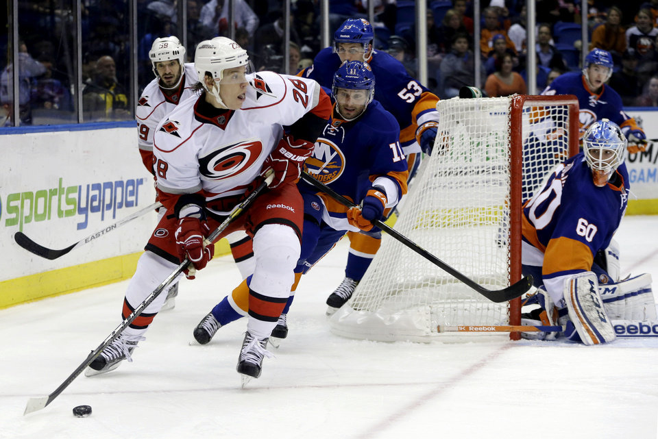 Carolina Hurricanes left wing Alexander Semin (28), of Russia, looks to pass as New York Islanders defenseman Lubomir Visnovsky (11), of Slovakia, and center Casey Cizikas (53) pursue while goalie Kevin Poulin (60) defends the crease in the third period of their NHL hockey game at Nassau Coliseum in Uniondale, N.Y., Sunday, Feb. 24, 2013. The Hurricanes won 4-2. (AP Photo/Kathy Willens)