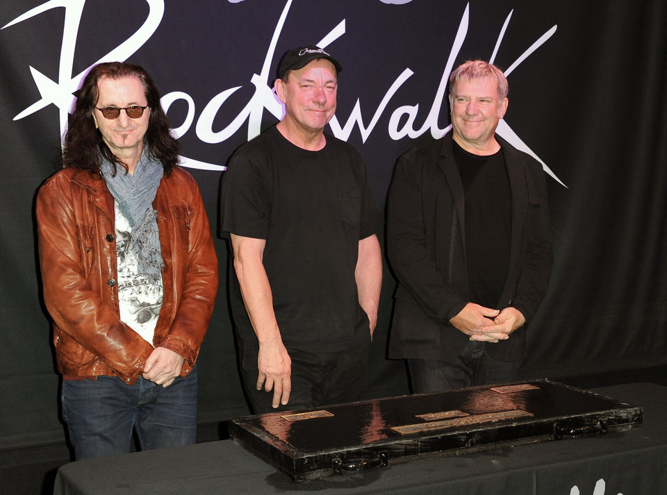 Photo - FILE - This Nov. 20, 2012 file photo shows members of the band Rush, from left, Geddy Lee, Neil Peart, and Alex Lifeson at the RockWalk induction of Rush at Guitar Center in Los Angeles. The eclectic group of rockers Rush and Heart, rappers Public Enemy, songwriter Randy Newman,