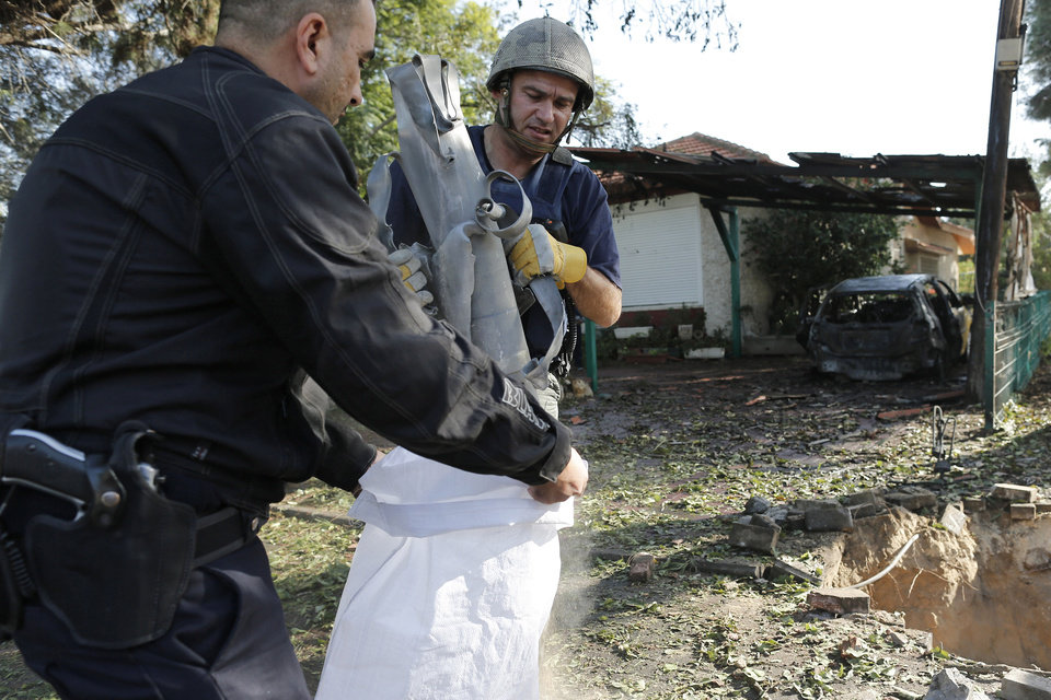 Israeli police sappers remove the remains of a rocket fired by Palestinian militants from Gaza Strip, that hit a house in Ashkelon, southern Israel, Sunday, Nov. 18, 2012. Israel launched the operation last Wednesday by assassinating Hamas� military chief and carrying out dozens of airstrikes on rocket launchers and weapons storage sites. Over the weekend, the operation began to target Hamas government installations as well, including the offices of its prime minister. (AP Photo/Tsafrir Abayov)