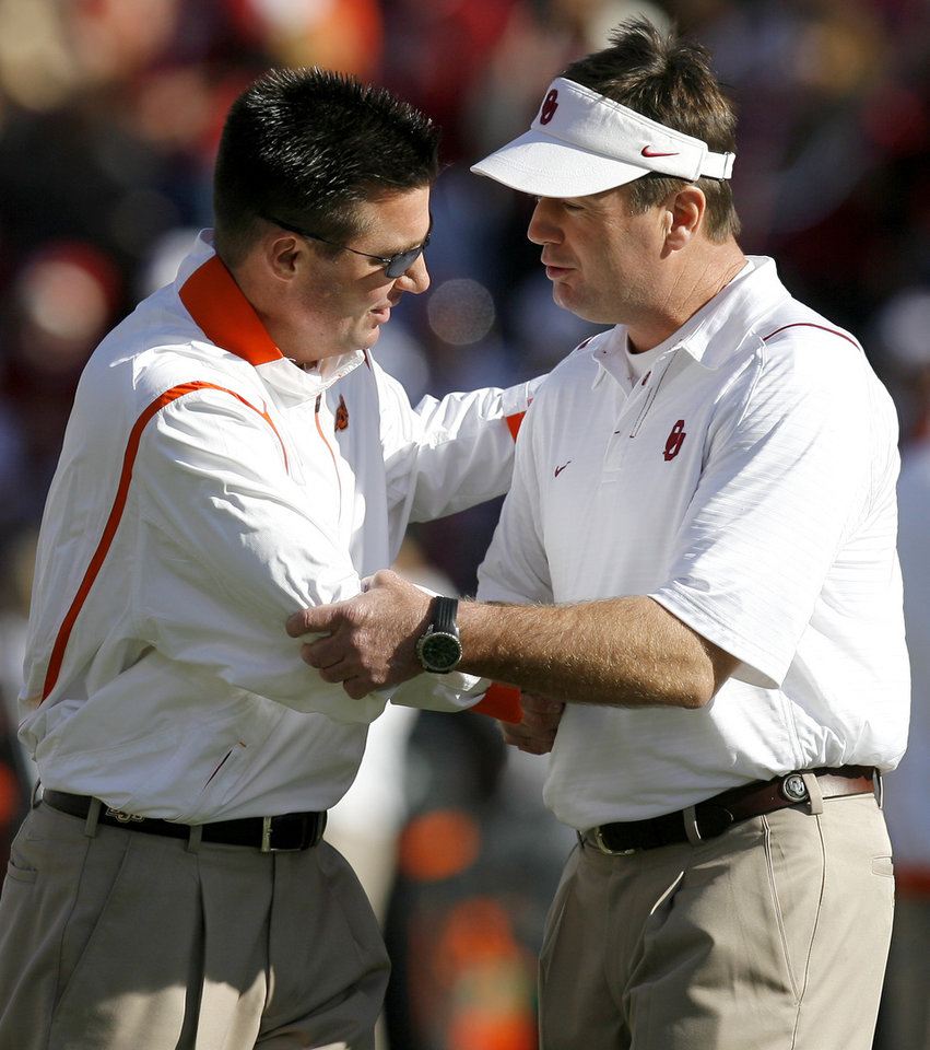 Photo - OSU coach Mike Gundy, left, and OU coach Bob Stoops meet before the Bedlam college football game between the University of Oklahoma Sooners (OU) and the Oklahoma State University Cowboys (OSU) at the Gaylord Family-Oklahoma Memorial Stadium on Saturday, Nov. 28, 2009, in Norman, Okla.
