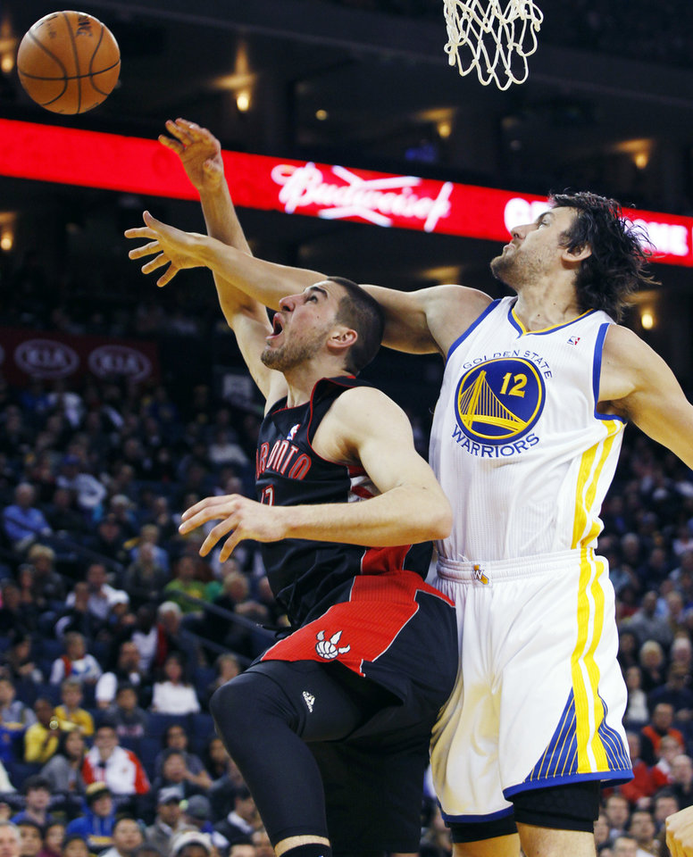 Photo - Toronto Raptors' Jonas Valanciunas, left, shoots as Golden State Warriors' Andrew Bogut defends during the first half of an NBA basketball game in Oakland, Calif., Monday, March 4, 2013. (AP Photo/George Nikitin)